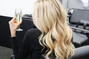 Bubbles and Blow Outs Offer at Regis Woman with Blonde Hair and Champagne